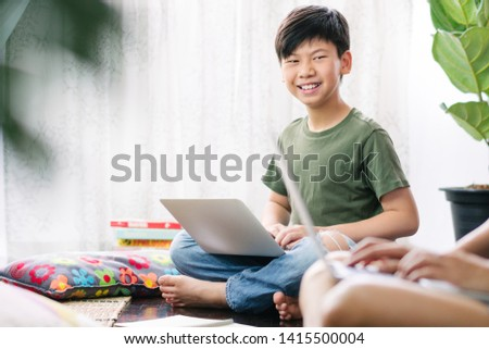 Smart looking Asian teenage boy using computer laptop, sitting on wooden floor, smiling, discussing with friends about group work, homework, exam preparation. Group work and collaboration. Stockfoto ©