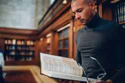 Smart male historian concentrated on scientific research working with literature in archive, clever young professor reading book in public library using information for intellectual project