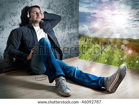 smart man leaning against a wall, listening to relaxing music
