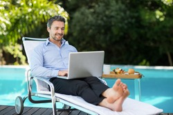 Smart man relaxing on sun lounger and using a laptop near the pool