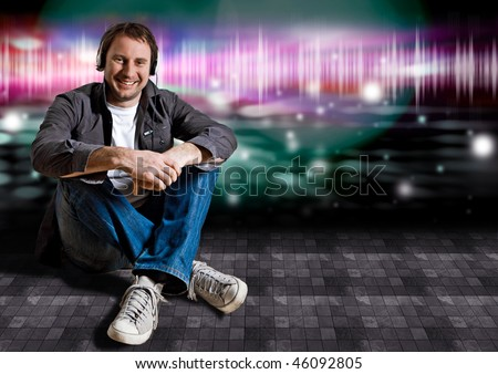 smart man sitting on the floor in a disco and listening to good music