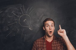 Smart man with raised finger on the background of blackboard with drawn lampbulb