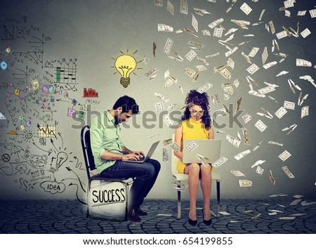 Smart man working on computer generates ideas next to a woman using laptop under money rain