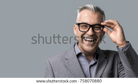 Smart mature businessman with glasses posing on gray background, he is smiling at camera