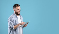 Smart millennial guy in glasses using tablet computer over blue studio background, banner design with copy space. Cheerful young man working, studying or communicating online