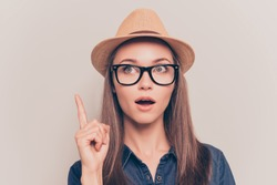 Smart minded woman with raised finger having an idea