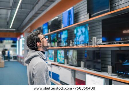 Smart modern male customer choosing large TV-sets at electronics store. He looks wondered. New screen generations.