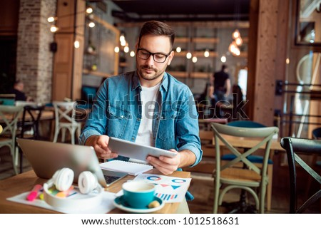 Smart modern young man working remotely from cafe #1012518631