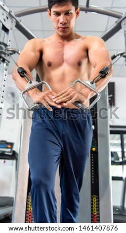 Smart muscular sporty asian man exercising building muscle .Young fitness guy execute exercise training with exercise-machine cable cross over in gym ,work out time