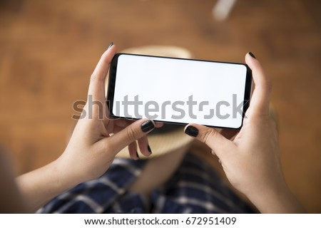 Smart phone Grey Color. Young Women with black nail polish playing with mobile phone on rustic brown wood background. Blank White Screen.