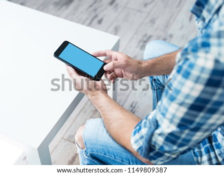Smart phone in male hands, at home. Clipping path included. stock photo