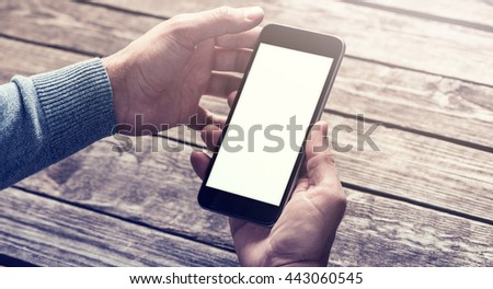 Smart phone in male hands over table. Clipping path included. stock photo