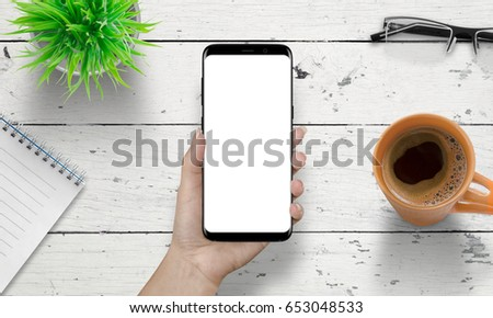 Smart phone in woman hand with isolated white screen for mockup. Wooden white desk in background with cup of coffee, plant, glasses beside.