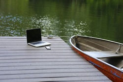 Smart phone & laptop computer on wood dock with aluminum rowboat & lake water in the background