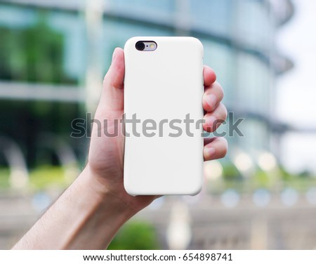 Smart phone on a blurry city background. in a white plastic case back view. Smart phone in man's hand. Template of iphone case. Mock up of phone case