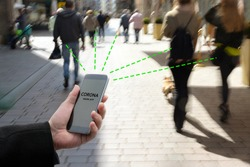 Smart phone with Corona Warn App, a contact tracking or tracing application against Covid 19 pandemic is connecting other phones from moving people in the city to analyze the risk of infection