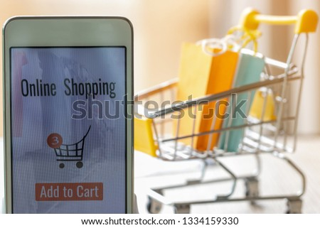Smart phone with goods and text add to cart on screen and paper shopping bags in trolley behind. Consumer can buy products directly anywhere anytime from seller. Online shopping and e-commerce concept