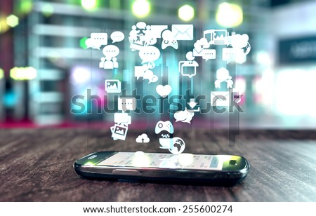Smart phone with social media related icons glowing over screen and soft focus.