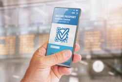 Smart phone with vaccine passport on screen for traveling with blurred background of flight schedule posters