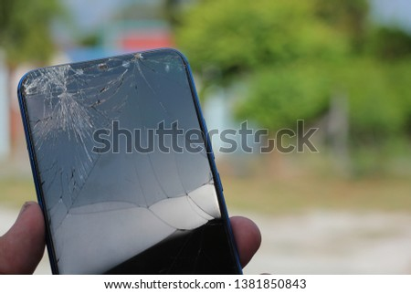 Smart phones have cracked screens in the hands of people.