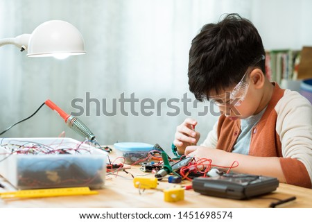 Smart preteen / teenage Asian boy screwdrivering, assembling and fixing computer chip, electronics hardware and circuits for school project with concentration and determination on desk. STEM Education