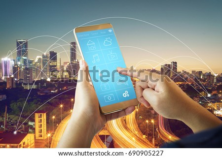 Smart remote home control system apps on a hand phone with city scape and network connection background . #690905227