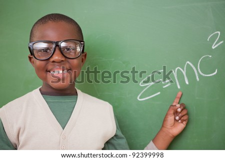 Smart schoolboy showing the the mass-energy equivalence formula on a blackboard