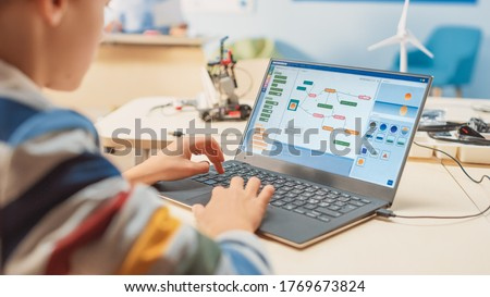 Smart Schoolboy Uses Laptop to Program Software for Robotics Engineering Class. Elementary School Science Classroom with Gifted Brilliant Children Working with Technology