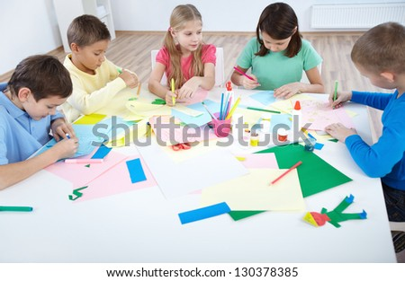 Smart schoolboys and schoolgirls drawing with colorful highlighters in classroom