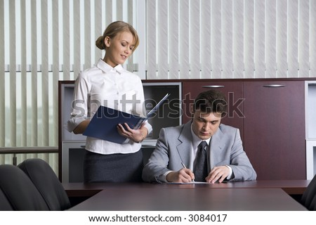 Smart secretary is giving documents to her boss for signing