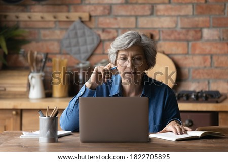 Smart senior grey-haired woman in glasses sit at table at home kitchen look at laptop screen working online. Mature Caucasian 60s female study or watch webinar on computer using internet connection.