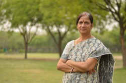 Smart senior north Indian woman standing, posing for the camera with hands crossed in a park wearing white/grey saree in summers in New Delhi, India