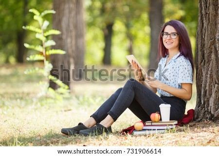 Smart student lady reading books and relaxing on a park background. Education concept. Copy space.