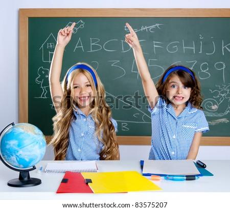 smart students in classroom raising hand with blackboard