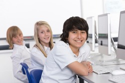 Smart students in computer class smiling at the camera while working on desktop computers