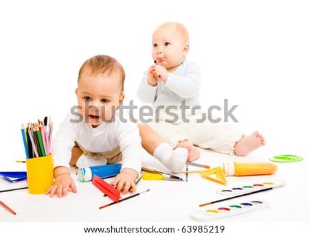 Smart toddlers with paints and paintbrushes