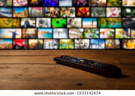 smart tv interactive television - channel collage with remote control on the table Stock photo ©