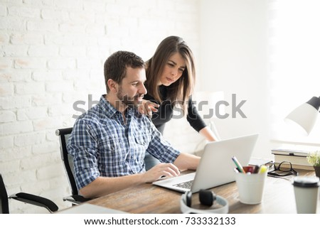 Smart woman giving some feedback about a project to her business partner in an office