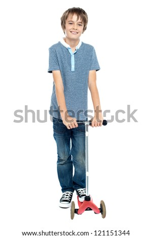 Smart young boy posing with his push scooter. Isolated against white background.