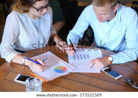 Smart young business men one woman suits sitting on table documents, graphics, technology,  Leaf catalog pages. Team entrepreneurs negotiate, discuss issues, solve problems, agree, talk #573521509