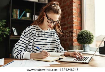 Smart young female entrepreneur in glasses and casual clothes working at laptop while sitting at table   and reports and writing in notebook against blurred interior of contemporary office