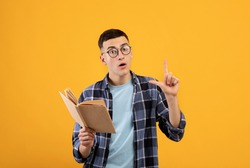 Smart young guy with book showing off his intelligence, gesturing eureka, having creative idea on orange studio background. Portrait of clever millennial student with textbook
