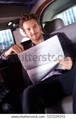 Smart young man reading newspaper in limousine, smiling.