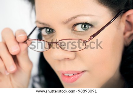 Smart young woman face overlooking her eyeglasses,close-up