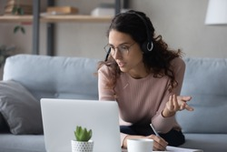 Smart young woman in glasses wearing wireless headphones with mic, looking at laptop monitor. Focused millennial female student watching online educational webinar, writing notes, studying at home.