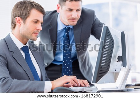 Smartly dressed young businessmen using computer at office desk #168172901