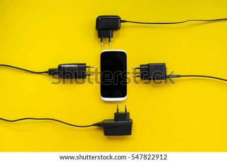 Smartphone and chargers around on a yellow background, concept. #547822912