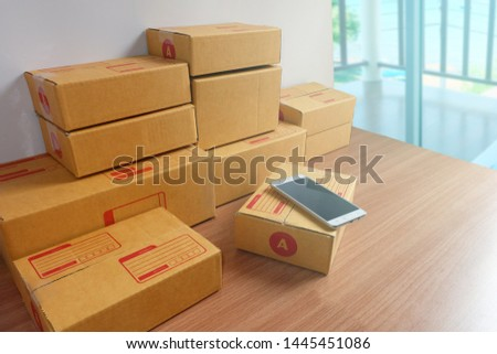 Smartphone and many product boxes on wooden floor, Online shopping, work at home, delivery, e-commerce concept.