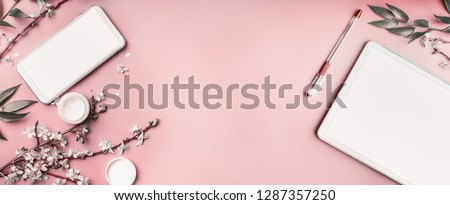 Smartphone and tablet pc mock up on pastel pink desktop background with cosmetic, stationery supples and white blossom branches, top view. Beaut blog and female business concept. Flat lay, banner Photo stock ©