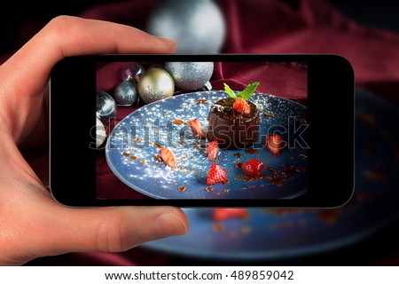 smartphone camera hand point shoot photo Christmas dessert pudding festive decorations Food photograph Home made food  for social networks. Top view mobile phone